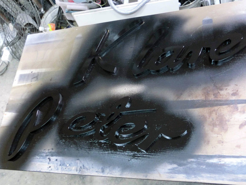 18_PETER-KLARE-SIGNAGE-fabrication-process-with-black-spray-paint-with-high-gloss